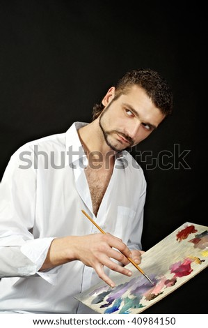 painter in a white shirt on a black background with a brush - stock photo