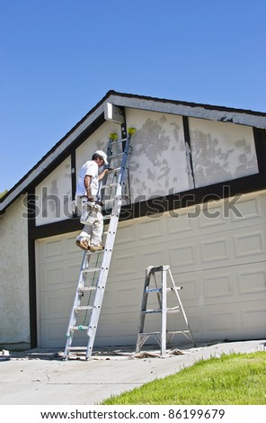 Painter makes his way up the ladder. - stock photo