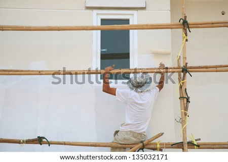 Painter on wooden scaffold painting wall by roller - stock photo