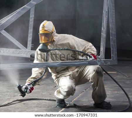 painter painting metal designs with airbrush - stock photo