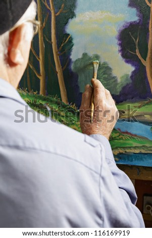 Painter painting picture in workshop rear view - stock photo