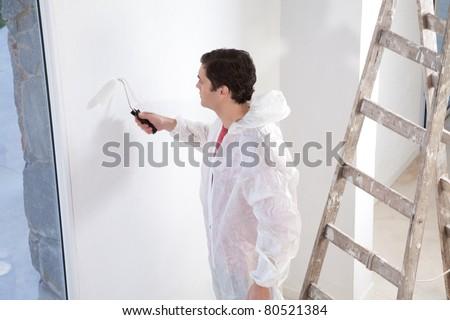 Painter painting the wall with roller