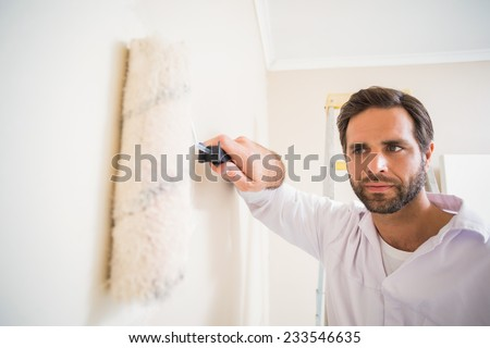 Painter painting the walls white in a new house