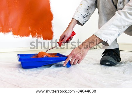 Painter refilling his paint roller whilst painting the walls in a room