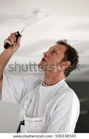 Painter repainting ceiling - stock photo
