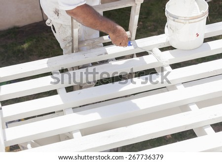 Painter Rolling White Paint Onto The Top of A Home Patio Cover. - stock photo