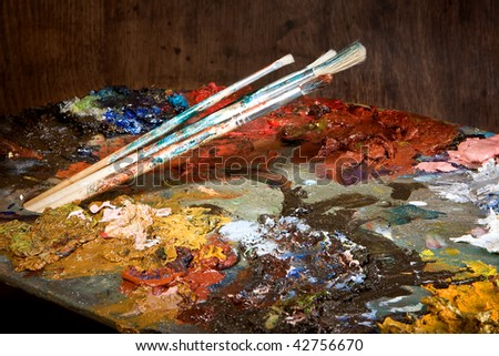 Painter's brushes and pallet full of colorful paint - stock photo