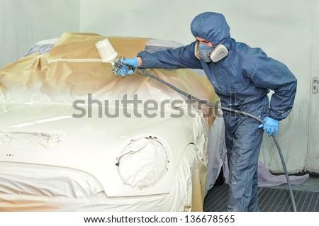 Painter spraying a white car bonnet. - stock photo