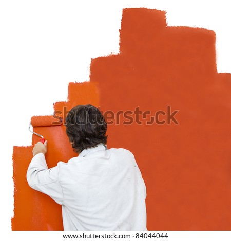 Painter using a paint roller to paint a wall orange