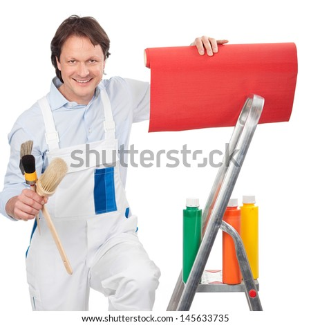 Painter with wallpaper and paints standing on a small metal stepladder in his white overalls smiling at the camera - stock photo