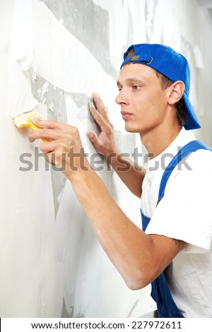 painter worker peeling off wallpaper from wall during interior home repair renovation work - stock photo