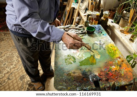 Painter working at palette in studio - stock photo