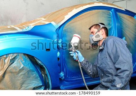 Painter working with blue car. - stock photo