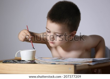 Painter Young boy learns how to paint - stock photo