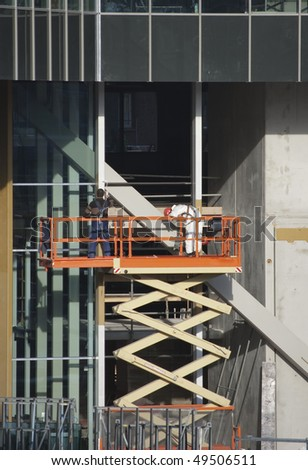 Painters wearing safety harness on a scissor lift - stock photo