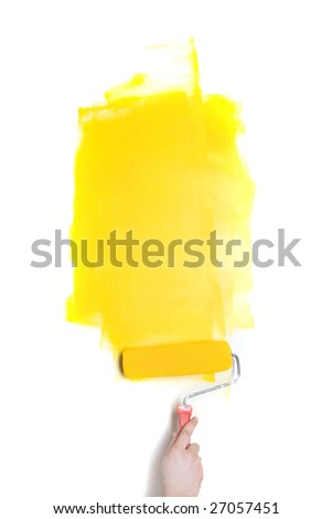 Paintig roller with yellow paint in human hand - stock photo