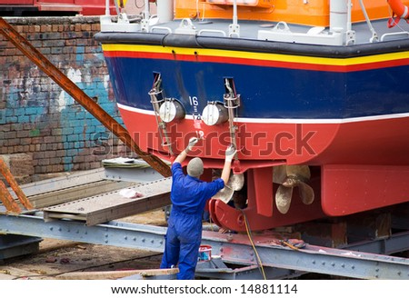 Painting a lifeboat in a Scottish harbour - stock photo