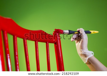 painting a red chair on green background - stock photo