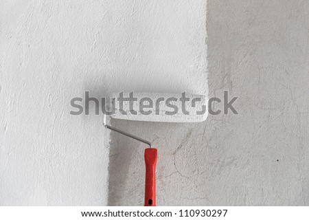 Painting a rough wall by painting roller and white latex. This stock image contains a paint roller in the center and half painted wall in the frame.