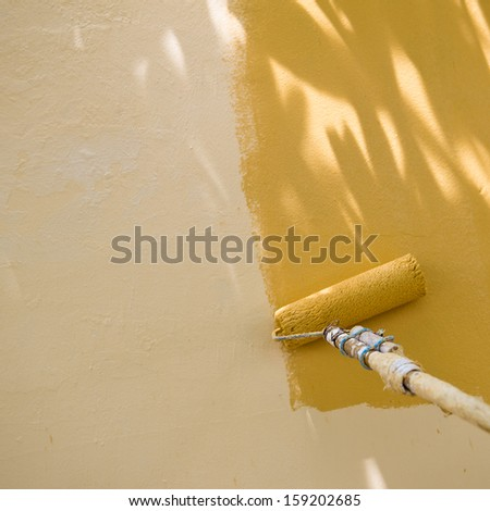 painting a wall with roller.  - stock photo
