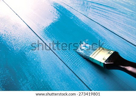 Painting a wooden shelf using paintbrush, blue color - stock photo