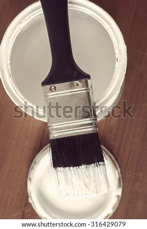 Painting and decorating a pot of white paint and brush with vintage effect filter applied to image - stock photo