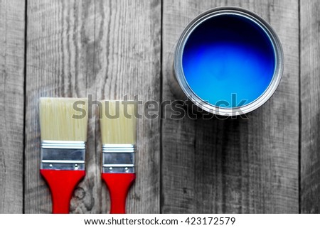 painting at home with can blue paint on wooden background