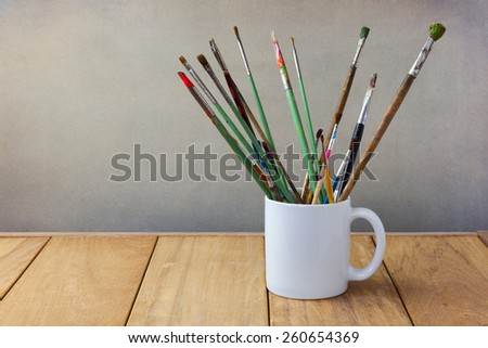 Painting brushes in white cup on wooden table - stock photo