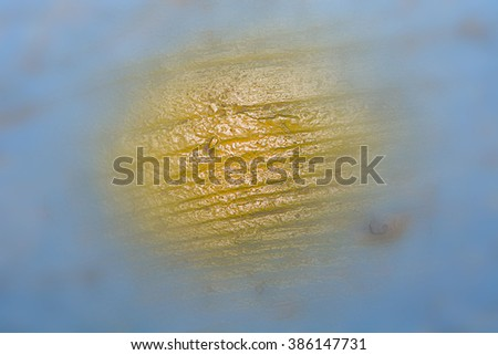 Painting concept. Old wooden blue wall with yellow circle of paint, blur blue wooden background, Circle or Bright Sky with Hazy Yellow Sun. - stock photo