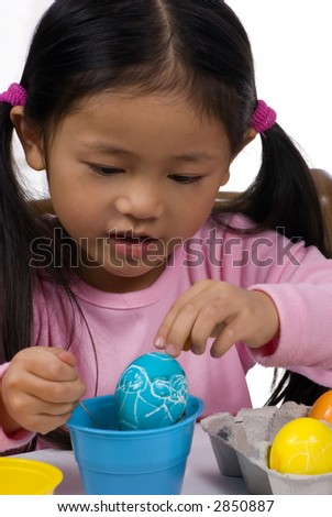 Painting easter eggs is so much fun... do you remember?  A young girl pull out an egg with her family painted on it. - stock photo