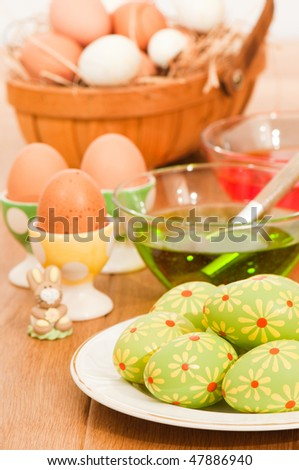 Painting Easter eggs with basket of eggs nestling in straw in background - stock photo