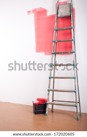 Painting equipment and the white stripe on the wall - stock photo
