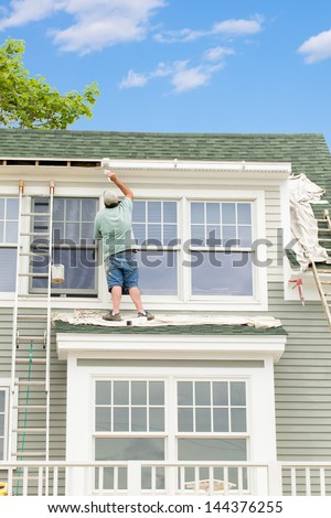 Painting exterior trim on a house - stock photo