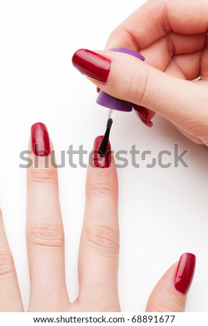 Painting female fingernails with red enamel close-up on white background
