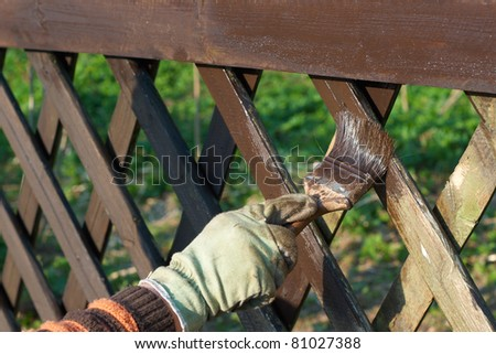painting fence in a brown color - stock photo