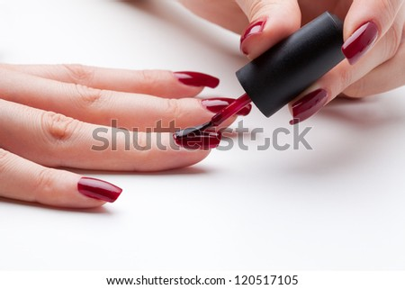 Painting fingernail with red enamel close-up - stock photo