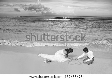 painting heart on the sand - black and white version - stock photo