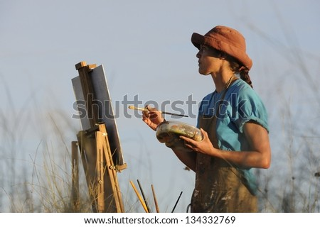 Painting in the landscape. Debbie Hilditch landscape painter on location - stock photo