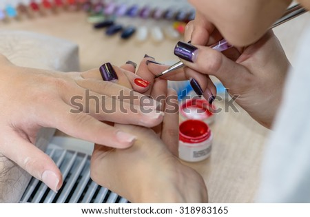 painting nails in nail salon, manicure, focus on the finger - stock photo