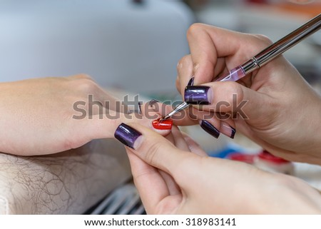 painting nails in nail salon, UV lap of quick dry nail polish manicure, focus on brush - stock photo