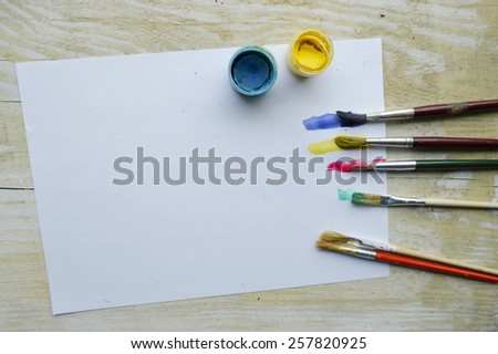 painting, paint, brushes for painting, landscape paper, creativity on the wooden background - stock photo