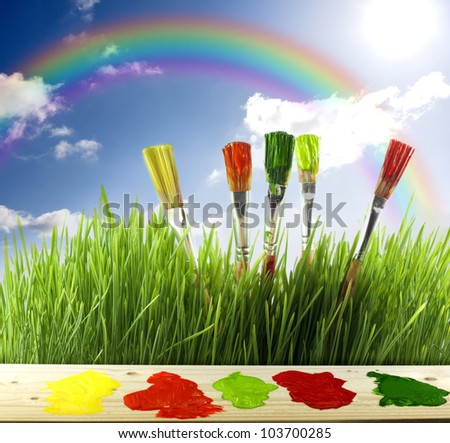 painting rainbow and grass and sky with colorful brushes - stock photo