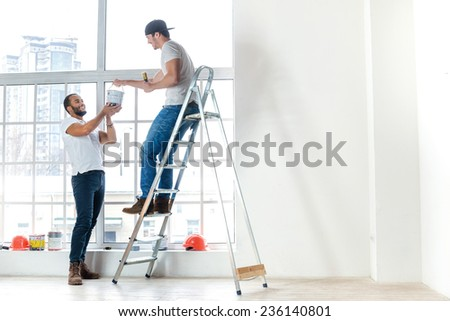 Painting, relocation and repairs in the apartment. Two workers make repairs in a new apartment. A Man takes the paint to another man on the ladder - stock photo