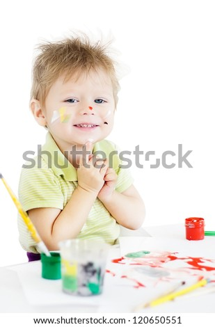 Painting smiling funny boy with color paints and brushes - stock photo