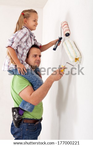 Painting the room with dad - little girl using paint roller playing piggyback with her father - stock photo