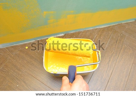 Painting the wall with paint roller - stock photo