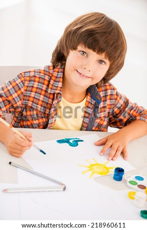 Painting. Top view of little boy relaxing while painting with watercolors sitting at the table - stock photo
