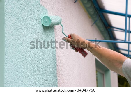 painting wall with a roll in green outdoor - stock photo