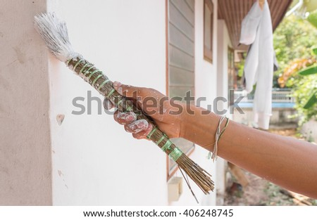 Painting walls.Painter paints using a brush,hand worker holding brush painting white on cement wall. (select focus hand ) - stock photo
