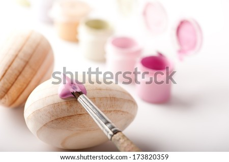 Painting with brush over wooden Easter eggs  - stock photo